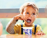 Little boy is eating yogurt, holding a spoon in his hand, sitting at the table .