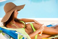 Beautiful young woman lying on deckchair by swimming_pool