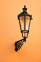 Wrought_iron lantern with its shadow on the yellow wall, Prague, Czech Republic