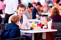 Young father and his two kids at outdoor cafe on autumn day