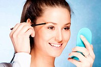 young woman apply shadow on eyebrows with brush, hold small mirror in other hand, studio shot