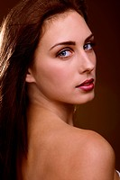 Face closeup of beautiful sensual woman looking over shoulder