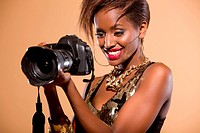 Attractive model in studio holding DSLR camera