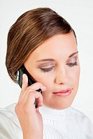 Head portrait of young smiling businesswoman talking on cellphone