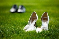groom and bride wedding shoes in the grass field
