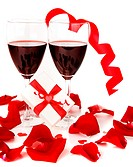 Romantic holiday gift, celebration with red wine with hearts ornament & ribbon decoration over white background