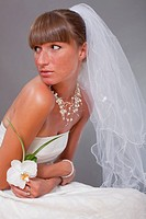 sensual bride with veil and flower posing in studio