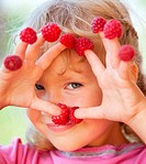 Happy little child with raspberry outdoors