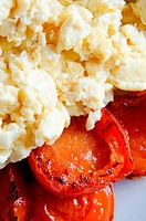 Close up macro of scrambled eggs and charred fried tomatoes on a white plate.