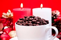 Christmas coffee beans in a cup over red background and Christmas decorations