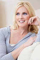 Portrait of a beautiful blond woman with blue eyes siting at home on a sofa or settee