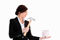 Businesswoman going to break a piggy_bank with a hammer against white background