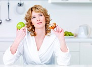 Thinking beautiful woman choosing between healthy food and caloric food _ indoors