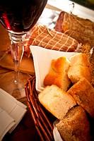 Closeup on homemade Italian bread, fine wine and salami.