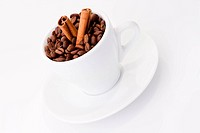 Coffee beans and cinnamon in white cup over white background. Shallow DOF.