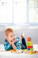 Adorable gingerish little boy laying on floor, playing with building cubes.