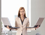Desperate businesswoman standing in bright office holding two laptops in hands.