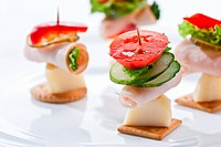 food theme: cracker with ham, cheese and vegetables on the plate