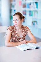 female college student in a library shallow DOF, color toned image