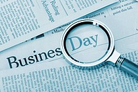 Loupe lies on the newspaper with title Business day. A photo close up. Selective focus