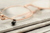 Eyeglasses lie on a pile of newspapers. A photo close up. Selective focus