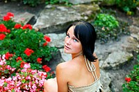 Portrait of young adorable woman is sitting near to beautiful flowers in central park at summer day at Bastion hill in Riga, Latvia
