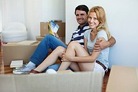 Couple unpacking in new house, man holding color swatches