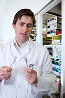 Wide_eyed engineer holding computer data cable in laboratory