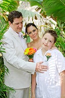 Wedding couple with boy under palms