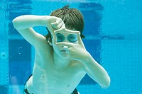Boy swimming underwater in swimming pool, hands forming finger frame