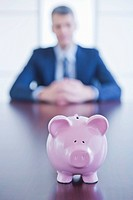 Piggybank on desk, businessman sitting on background