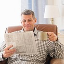 Man sitting in living room with newspaper and mug