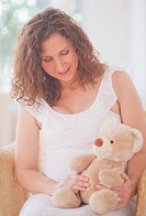 Portrait of pregnant woman with teddy bear