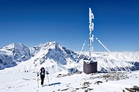 Cross country skier on the summit of Hintere Schoentaufspitze Mountain beside the weather station, looking towards the Ortler and Zebru Mountains, Sol...