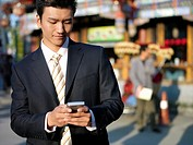 A young Chinese businessman in a suit checking his text messages or email on his mobile smart phone through wireless internet with traditional Chinese...