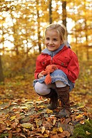 Girl on a tree stump covered with autumn leaves in the forest