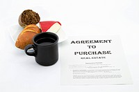 Agreement contract for real estate purchase is placed with coffee, cheese, and bread as a life event decision is weighed carefully