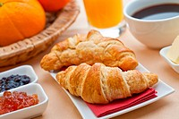 Continental breakfast with croissant, jam, coffee and orange juice