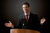 A businessman is standing at a podium with a microphone giving a lecture with outstretched hands. Horizontal shot.