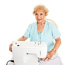 Beautiful senior woman enjoys sewing. Isolated on white.