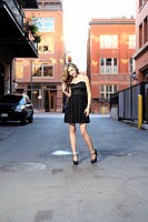 Young woman wearing a short black dress posing in an urban setting
