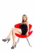Young woman in a short black dress posing in a red chair