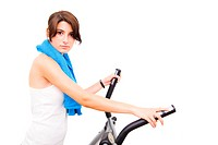 Young woman exercising on elliptical stepper against white background.