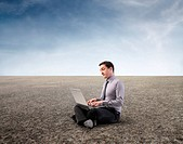 Businessman in a desert using a laptop