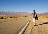 A man hitchhiking on rural desert highway