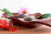 Massage stones on sand in a bowl, a purple flower and red bath salt isolated on white background