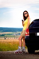A portrait of a young woman standing near the car with mobile phone on the roller skates in the country