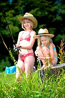two young girls in the straw hats fishing at the lake