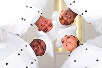 underneath view of group of professional chefs heads together for form a team