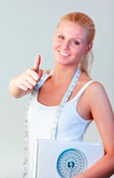 Beautiful blonde woman with thumb up holding a scales and smiling at the camera with focus on thumb